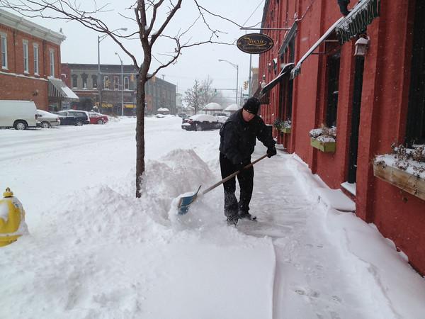 SCOTT WEISSER   The Goshen News<br /> Dave Widmer shovels snow along East Washington Street in downtown Goshen Wednesday morning.