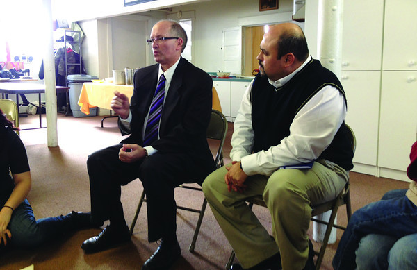 SCOTT WEISSER | The Goshen News<br /> Elkhart County Sheriff Brad Rogers, left, speaks during a community policing meeting Sunday at Iglesia Menonita Del Buen Pastor in Goshen. At right is church pastor David Araujo.