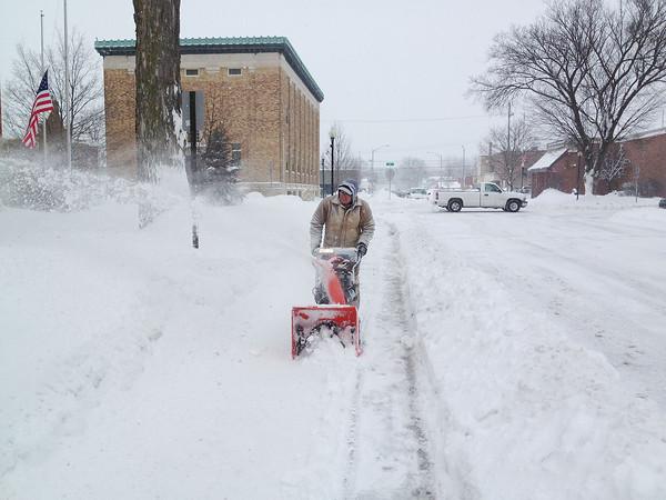 SCOTT WEISSER | The Goshen News<br /> Jeff Halsey clears snow along East Jefferson Street Wednesday morning.