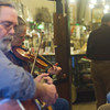 SAM HOUSEHOLDER | THE GOSHEN NEWS<br /> Bev Smith of Cassapolis, Mich. plays fiddle with the band Waterbound at the Goshen Historical Museum during First Friday Sweet Indulgence. Bandmate Steve Seegars, of Elkhart plays in the foreground.