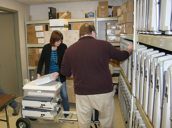 JOHN KLINE   THE GOSHEN NEWS<br /> Elkhart County Clerk Wendy Hudson, left, and Chad Clingerman, office manager of Voter Registration and the Elkhart County Election Board, right, load electronic touch screens and voting kits onto a dolly Friday morning before transporting them to one of the county's 25 new vote centers in preparation for Tuesday's Primary Election.