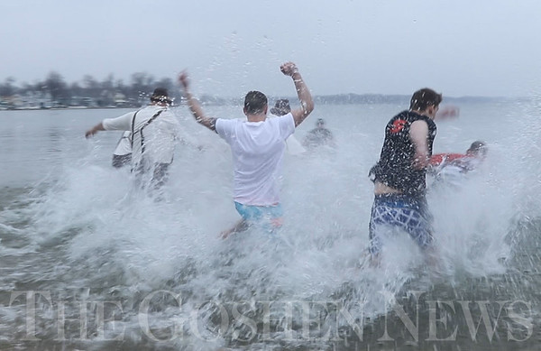 JAY YOUNG | THE GOSHEN NEWS<br /> Water splashes about as participants in the Polar Plunge run into the chilly water of Wawasee Lake at the Oakwood Resort during Wawasee Winter Carnival on Saturday in Syracuse.  Nine people took part in the plunge that benefitted Boomerang Backpacks.