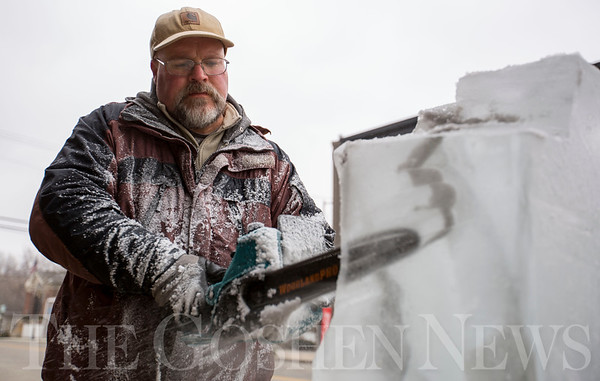 JAY YOUNG   THE GOSHEN NEWS<br /> Ryan Frauhiger uses a chainsaw to cut through a block of ice near the intersections of Main and Huntington streets during the Wawasee Winter Carnival on Saturday in Syracuse.  Frauhiger was carving a fish out of the ice.