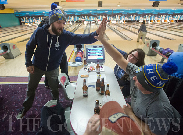 JAY YOUNG | THE GOSHEN NEWS<br /> Jesse Sensenig, left, gets a high-five from David Zehr after rolling a strike during the ninth annual Spare Time at the Chamber bowling event on Thursday afternoon at Maple City Bowling. The pair were representing Goshen Brewing Company. Twenty teams made up of five bowlers each took part in the event hosted by the Goshen Chamber of Commerce.