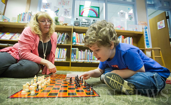 JAY YOUNG | THE GOSHEN NEWS<br /> Four-year-old Layne Miller studies the chess board intently after learning the names of the various pieces from children's librarian Tina Ervin following Storytime at the Goshen Public Library on Wednesday morning.