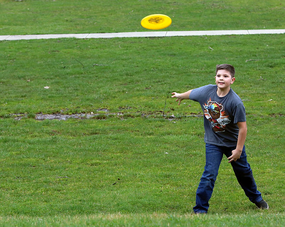 Roger Schneider | The Goshen News<br /> Noah Gans, 10, of Syracuse, lets fly with a Frisbee Sunday while playing catch with his family at Shanklin Park. The park was crowded with people who were seeking a day outside on a mild spring day.