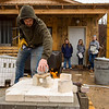 JAY YOUNG | THE GOSHEN NEWS<br /> Instructor Parker Hunt, of Goshen, places clay pots inside a raku kiln while his students try to stay dry on Wednesday afternoon during a demonstration that was part of a spring break arts camp hosted by Goshen Youth Arts.