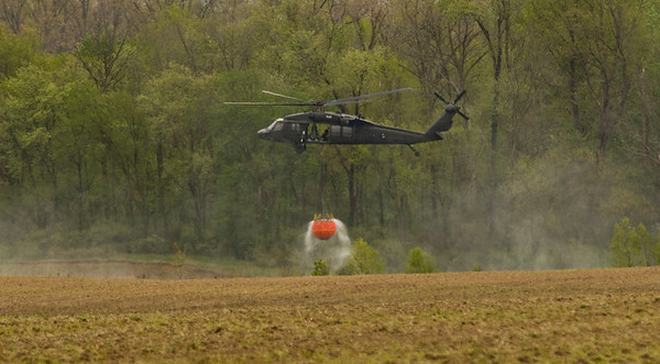 JAY YOUNG | THE GOSHEN NEWS<br /> A Blackhawk helicopter fills a water bucket at a pond on the property of Waste Management's Earthmovers landfill Thursday afternoon.