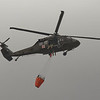 JAY YOUNG | THE GOSHEN NEWS<br /> A Blackhawk helicopter carrying a water bucket flies overhead near the fire at Waste Management's Earthmovers landfill Thursday afternoon.