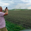 Roger Schneider | The Goshen News Tim Kelly uses his phone along C.R. 7 Wednesday afternoon to broadcast a video of the fire at the Waste Management landfill.