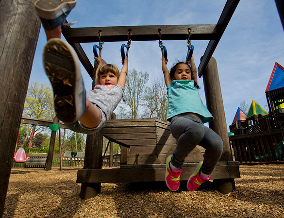 JAY YOUNG | THE GOSHEN NEWS<br /> Four-year-old Aubrey Triplett, left, and Kaia Kennedy, 5, both of Goshen, enjoy Monday's mild weather as they swing from the monkey bars in Shankin Park.  The National Weather Service forecasts the mild temperatures to continue through the end of the week. However, expect the clear skies will give way to clouds and rain by Thursday.