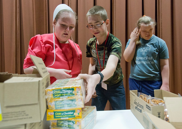 JAY YOUNG   THE GOSHEN NEWS<br /> Westview Jr.-Sr. High students Kathy Troyer, left, and Gavin Fulks reach for cheese filled crackers while Jessica Fredrick watches  Thursday morning at Topeka Elementary School. The three were filling up plastic bags with food for Boomerang Backpacks.