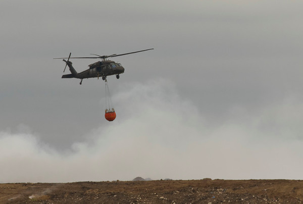 JAY YOUNG | THE GOSHEN NEWS<br /> A Blackhawk helicopter carrying a water bucket flies over the fire at Waste Management's Earthmovers landfill Thursday afternoon.