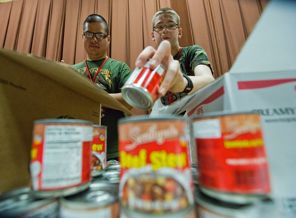 JAY YOUNG | THE GOSHEN NEWS<br /> Westview Jr.-Sr. High freshman Gavin Fulks reaches for a can of beef stew while senior Alex Sanchez watches as the pair fill up bags with food for Boomerang Backpacks as part of their functional skills class Thursday morning at Topeka Elementary School.