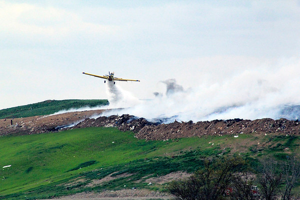 Roger Schneider | The Goshen News<br /> A cropduster pilot drops water upwind of the fire atop the Waste Management's Earthmovers landfill so the water will drift back into the blaze.