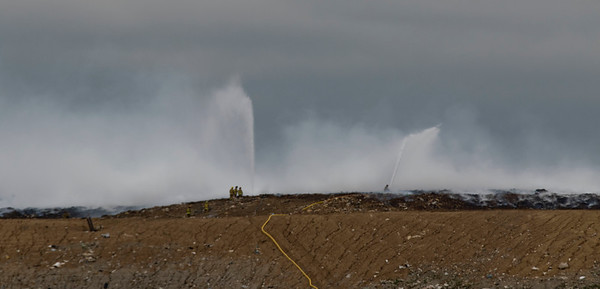 JAY YOUNG | THE GOSHEN NEWS<br /> Area firefighters run hoses up the west side of Waste Management's Earthmovers landfill to fight the fire Thursday afternoon.