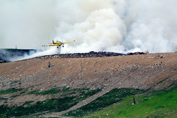 Roger Schneider | The Goshen News<br /> A cropduster pilot drops a load of water on the fire at the Waste Management landfill Wednesday afternoon.