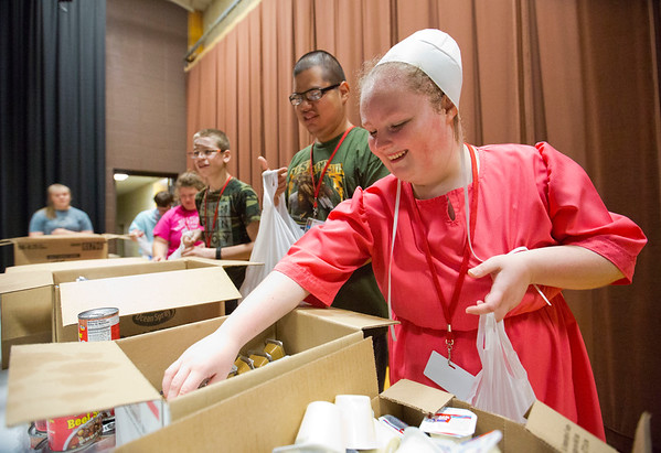 JAY YOUNG | THE GOSHEN NEWS<br /> Westview Jr.-Sr. High School freshman Kathy Troyer flashes a smile as she reaches for peanut butter to put in her Boomerang Backpack food bag during her functional skills class Thursday morning at Topeka Elementary School.  The three were filling up plastic bags with food for Boomerang Backpacks.