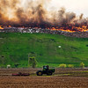 JAY YOUNG | THE GOSHEN NEWS<br /> A farmer uses a tractor to work his field as a fire rages in the background at Waste Management's Earthmover landfill, located at 26488 C.R. 26, Wednesday morning.