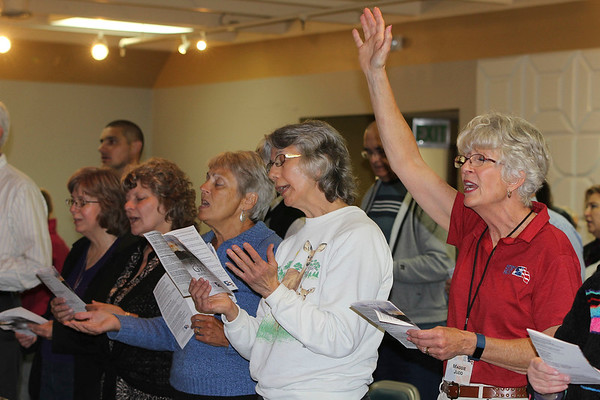 SHEILA SELMAN | THE GOSHEN NEWS<br /> Maggie Judd lifts her hand in worship during singing at National Day of Prayer at Life Spring Church in downtown Goshen Thursday afternoon.