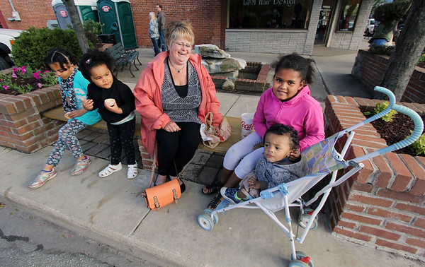 JULIE CROTHERS BEER | THE GOSHEN NEWS<br /> Brenda Cripe of Goshen stops for a pretzel snack with her grandchildren, from left, Toluope Busari, 7, Olatundun Busari, 3, Yetunde Busari, 9, and Money Busari, 1, during First Fridays in Goshen.