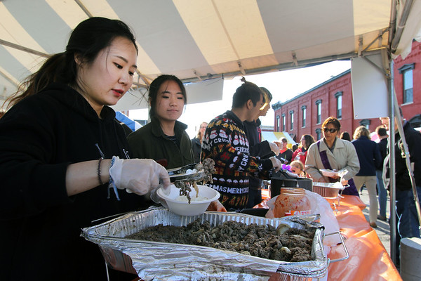 JULIE CROTHERS BEER | THE GOSHEN NEWS<br /> Goshen College students Ming Woo, Yejin Kim, Phil Chan and Byeong Min Lim serve Korean food during Goshen's First Fridays. Woo said the students made all of the items, including the Bulgogi, a Korean barbecue dish, she was serving.