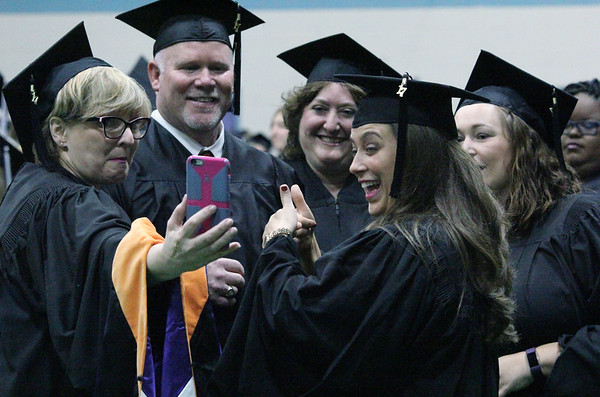 JULIE CROTHERS BEER | THE GOSHEN NEWS<br /> A group of Goshen College graduates pose for a selfie before walking into the gymnasium Sunday for commencement.