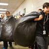JAY YOUNG | THE GOSHEN NEWS<br /> Model Elementary fifth-grader Carlos Cervantes, along with his classmates, carry black garbage bags full of plastic grocery bags they collected for The Window Tuesday afternoon at the school. Over the course of five days, students at the school collected 9,749 bags total. The Window uses about 100 bags every day for clients to carry their items. The project began as a service learning project for first grade students at the school to learn about reducing, recycling and reusing items, but soon spread to include all grades.