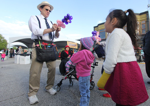 JULIE CROTHERS BEER | THE GOSHEN NEWS<br /> Balloon artist Steve Coyne finishes a purple flower with a pink stem for Audrey Wallach, 6, of Syracuse during Goshen's First Fridays.