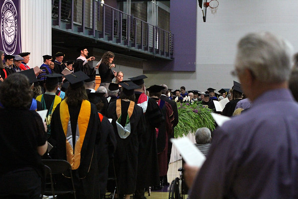 JULIE CROTHERS BEER | THE GOSHEN NEWS<br /> Goshen College faculty, students and graduation attendees sing along as Scott Hochstetler, associate professor of music at GC, leads them in a hymn during the 2017 commencement ceremony Sunday.