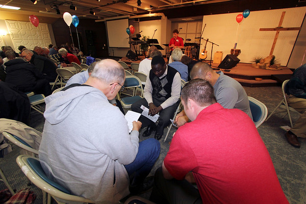 SHEILA SELMAN | THE GOSHEN NEWS<br /> Praying in a small group at Life Spring Church in Goshen are, starting at right with the man in the gray shirt and going counter-clockwise, are Jerry Lehman of Middlebury; Theo Odhiambo, Elkhart; Steve Loft, Jimtown (obscured); Ted Conley, Shipshewana; and Aaron Miller, Middlebury.