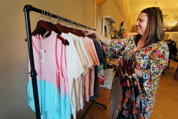 JULIE CROTHERS BEER | THE GOSHEN NEWS<br /> Amber Huber adds clothing to the rack during Boho Pretty's open house event Friday. Store owners Huber and Mary Miller hosted the shop's grand opening during Goshen's First Fridays.