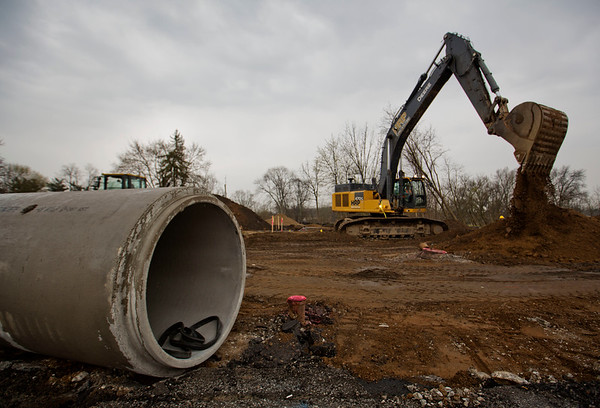 JAY YOUNG | THE GOSHEN NEWS<br /> Despite light rain Thursday morning, construction crews continued working on the U.S. 33 realignment project on Pike Street. Workers were installing 48 inch drainage pipes just east of the Pike Street bridge over the Elkhart River.