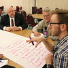 SHEILA SELMAN | THE GOSHEN NEWS<br /> Seth Miller of Goshen College, right, takes notes in a discussion group with Indiana State Board of Education member Byron Ernest, left, and Goshen College professor emeritus Marvin Bartel Tuesday night at Goshen College.