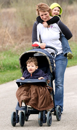JAY YOUNG | THE GOSHEN NEWS<br /> Four-year-old Keaton Kaufman catches a ride piggyback style from his mom, Shelby, while his brother Quinton, 2, all of Elkhart, gets pushed along as they take part in mommy stroller meetup group Monday morning at Oxbow Park.
