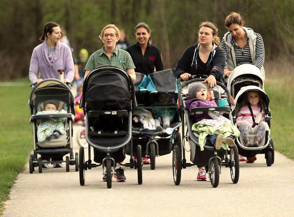 JAY YOUNG | THE GOSHEN NEWS<br /> Rachel Cunningham, left, and Wendy Yankovich pick up the pace as rain falls while they walk around Oxbow Park Monday morning during a mommy stroller meetup group.