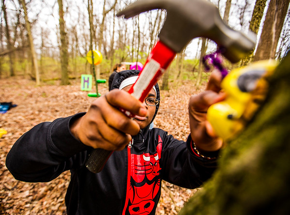 JAY YOUNG | THE GOSHEN NEWS<br /> Merit Learning Center senior JenDaia Greer hammers a plastic ladybug to a tree Tuesday morning at LoveWay in Middlebury. Students from the school, who were working on their service learning project, decorated the sensory riding trail with colorful art.