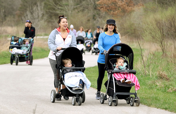 JAY YOUNG | THE GOSHEN NEWS<br /> Kristin Troup, left, pushes her son Beckett, 2, both of Elkhart, as she chats with Halie Ebenroth, who is pushing her two-year-old daughter Kendalyn, both of Goshen, while they walk around Oxbow Park Monday morning during a mommy stroller meetup group.