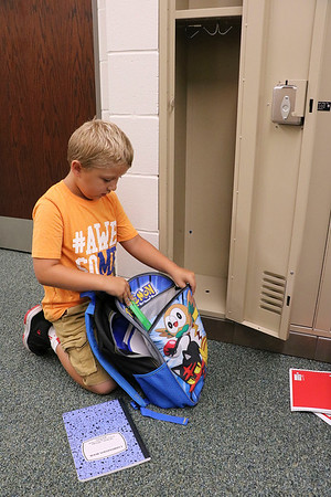 SHERRY VAN ARSDALL | THE GOSHEN NEWS<br /> Second-grader Lawson Anglin takes out his school supplies from his backpack during the first day of school in the new building at Syracuse Elementary School Thursday.
