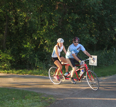 SHEILA SELMAN | THE GOSHEN NEWS<br /> Hannah and her dad Michael Yeakey bike in tandem along the Pumpkinvine Nature Trail Saturday morning. They were continuing a tradition of particiipating in the Quilt Gardens Ride, formerly Bloom & Zoom.