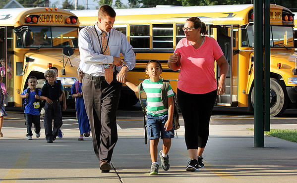 JULIE CROTHERS BEER | THE GOSHEN NEWS<br /> Holding hands with kindergarten student Avery Hostetler, Nappanee Elementary School Principal Randy Cripe checks his watch as school buses arrive for the first day of school Wednesday. To the right is Jenni Heeter.
