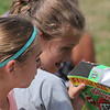 Roger Schneider | The Goshen News<br /> Halle Ganger, right, and Layla Miller, Concord Intermediate School fifth-graders, view the solar eclipse Monday using a viewer made from a cerial box.