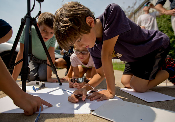 JAY YOUNG | THE GOSHEN NEWS<br /> Bethany Christian fifth-grade- student Emerson Landis, along with other classmates, watches the progress of the moon passing in front of the sun as Monday's solar eclipse is projected onto a sheet of paper.