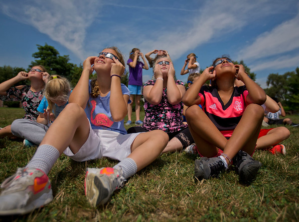 JAY YOUNG | THE GOSHEN NEWS<br /> Bethany Christian sixth grade students, from left, Mariah Stoltzfus, 12, Megan Hanton, 11, and Eva Horning, 11, sport eclipse glasses as they sit outside the school Monday afternoon to watch the solar eclipse as it reaches its peak just before 2:22 p.m.