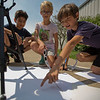 JAY YOUNG | THE GOSHEN NEWS<br /> Binoculars project the progress of the moon while it passes in front of the sun onto a sheet of paper during Monday's solar eclipse as Bethany Christian fifth-grade students, from left, Nestor Sanchez, Sorel Miller and Emerson Landis watch.