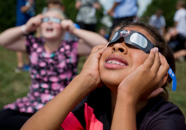 JAY YOUNG | THE GOSHEN NEWS<br /> Bethany Christian sixth grade students Eva Horning, 11, foreground, and Megan Hanton, 11, watch the solar eclipse Monday afternoon on the front lawn of the school.