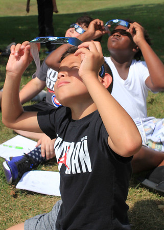 Roger Schneider | The Goshen News<br /> Concord sixth-graders Emiliano Mejia-Moacedo, front, Jamari Williams, in white shirt and Jack Berry in back, check out their eclipse viewing glasses as the solar event begins Monday.