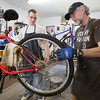 JAY YOUNG | THE GOSHEN NEWS<br /> Les Gustafson-Zook, right, shows Matthew Lemons how to true the rear tire on a mountain  bike Wednesday morning at Chain Reaction Bicycle Project, 510 East Washington Street. Lemons was at the shop to find a bicycle for himself. The shop allows anyone to work off the price of a bicycle by working in the shop.