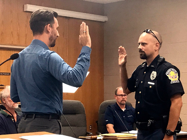 JOHN KLINE | THE GOSHEN NEWS<br /> Goshen Mayor Jeremy Stutsman, left, promotes Kyle L. Kalb to the rank of sergeant with the Goshen Police Department during a meeting of the Goshen Board of Public Works and Safety Monday afternoon.