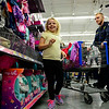 BEN MIKESELL | THE GOSHEN NEWS<br /> Ariya Barkdull, 7, of Goshen, laughs with Goshen police officer Don Daeschler while picking out doll clothes during Wednesday's Cops and Kids event at Walmart on Elkhart Road. Officers from Goshen, Nappanee and Wakarusa volunteered to shop with kids from their communities.